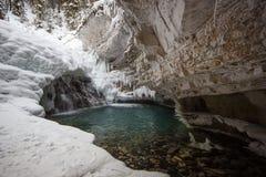 冻瀑布和明白冷水连续throug河狼吞虎咽,约翰斯顿峡谷,班夫国家公园,加拿大 免版税库存图片
