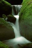 瀑布和生苔岩石 免版税库存照片