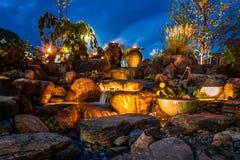 瀑布喷泉风景在与光的晚上 免版税库存照片