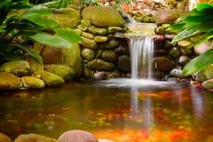 瀑布在一个小池塘在庭院里 免版税库存照片