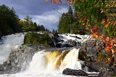 瀑布在与多云天空和桔子叶子的秋天 免版税库存照片