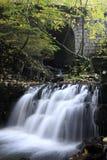 瀑布在Satina河的石桥梁下 库存图片