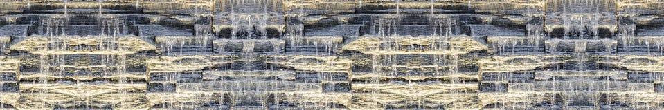瀑布无缝的全景黑暗的背景在石墙上的 免版税库存图片