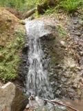 瀑布是小的在山之间 免版税库存照片
