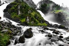 瀑布的水流动入在两个不同的方式的绿色山谷 地面石头和绿草a岩石和有很多 图库摄影