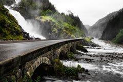 瀑布的水流动入在两个不同的方式的绿色山谷 地面石头和绿草a岩石和有很多 库存图片