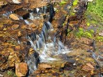 瀑布的特写镜头与金黄色的岩石和青苔的 免版税库存图片