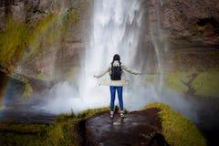 瀑布的背景的年轻女性游人 免版税库存照片