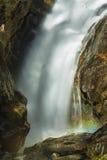 瀑布的被弄脏的行动与一条彩虹的在薄雾 免版税库存图片