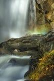 瀑布的被弄脏的行动与一条彩虹的在薄雾 免版税库存照片