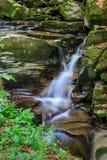 瀑布的边缘在的与青苔的崎岖的石头 库存图片