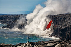 瀑布的顶面部分空中白天看法塑造了红色熔岩流程从火山的在下面夏威夷和多岩石的海滩 免版税库存照片
