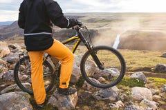 瀑布背景的愉快的骑自行车的人在山的 冰岛 免版税库存照片