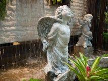 瀑布逗人喜爱的一点丘比特雕塑infront  图库摄影
