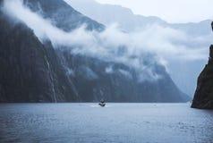 瀑布,小瀑布,在Milford Sound的划船 免版税库存照片