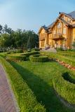 灌木和花构筑的美丽的绿色草坪在一个大富有的豪宅,亚努科维奇博物馆住所前面  免版税库存照片
