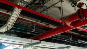 火与垂悬从在大厦里面的天花板的红色管子的洒水装置 扑火 消防和探测器 主要 免版税库存照片