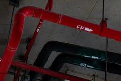 火与垂悬从在大厦里面的天花板的红色管子的洒水装置 扑火 消防和探测器 主要 库存图片