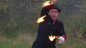 火人在他自己附近在秋天扭转两个被点燃的爱好者户外在slo mo 影视素材