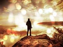火光,软的焦点 摄影师与folden在峭壁认为的结尾的三脚架 重的老保守风景, 库存照片