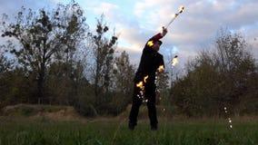 火变戏法者在他自己附近在秋天扭转两个被点燃的爱好者户外在slo mo 股票录像