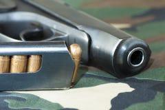 火器手枪和手开枪在军事伪装背景的弹药 免版税库存图片