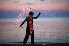 火在日落天空背景的舞蹈家剪影 免版税图库摄影