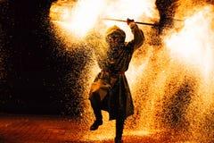 火展示在晚上 年轻人在观众前面站立 库存照片