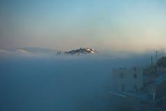 破火山口峭壁上面在雾在晴朗的日出, Imerovigli,圣托里尼海岛村庄上的  库存图片