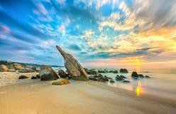 火山岩在与剧烈的天空的日出靠岸,在礁石下 免版税库存图片