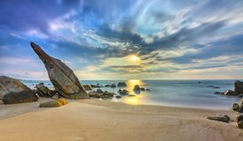 火山岩在与剧烈的天空的日出靠岸,在礁石下 图库摄影