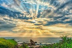 火山岩在与剧烈的天空的日出靠岸,在礁石下 库存照片