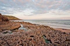 火山岩在Gower,威尔士的海滩日落 免版税库存照片