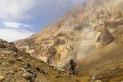 火山岩背景的年轻摄影师  Kamchatk 免版税库存图片