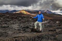 火山岩背景的年轻旅客  免版税库存照片