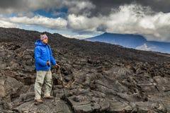 火山岩背景的年轻旅客  库存图片