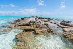 火山岩道路到海洋里,Aitutaki 免版税库存照片