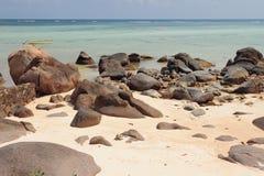 火山的冰砾和石头在沙滩 Mahe,塞舌尔群岛 免版税库存图片