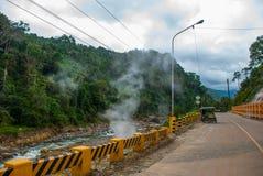 从火山的山的白色蒸汽和穿过有一辆摩托车的路有边车的 菲律宾 巴伦西亚,海岛Ne 库存图片