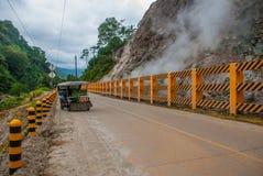 从火山的山的白色蒸汽和穿过有一辆摩托车的路有边车的 菲律宾 巴伦西亚,海岛Ne 免版税图库摄影