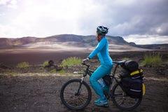 火山的山背景的愉快的骑自行车的人在冰岛 库存照片