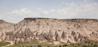 火山的峡谷的,土耳其被放弃的洞房子 库存图片