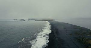 黑火山的海滩的鸟瞰图在冰岛 飞行在海的美丽的岸的直升机有波浪的 影视素材