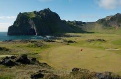 火山的风景的高尔夫球场与熔岩、山和海洋 免版税库存图片