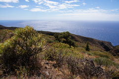 火山的风景,与峭壁和蓝色海 免版税库存图片