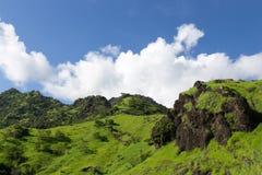 火山的绿色倾斜在蓝天背景的与云彩的 免版税图库摄影