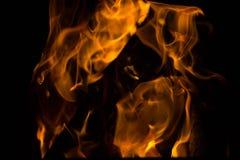 火火焰在黑背景的 在黑暗的火愤怒 篝火在晚上 火焰跳舞 免版税库存照片