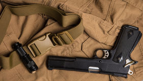 火炬和枪在棕色布料 库存照片