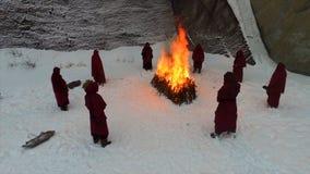 火炬队伍 礼节火 英尺长度 敞篷长袍的修士走沿冬天雪足迹的小组在森林里 免版税库存照片