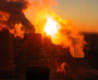 火热的日出在蒸汽云彩遮暗的一个冷的清早冬天  免版税库存图片